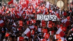 Tens of thousands of Bahrainis wave flags and carry a mock casket representing a recent dialogue rejected by many government opponents during a protest march in Saar, July 29, 2011