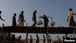 Rohingya refugees cross two bridges at Kutupalong refugee camp, near Cox's Bazar, Bangladesh, Nov. 28, 2017.