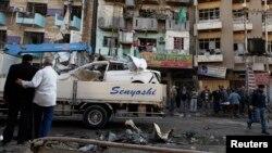 Warga Irak memeriksa lokasi serangan bom mobil di Baghdad, Senin (20/1).