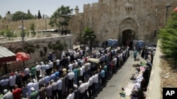 Palestinians pray outside the Lion's Gate in Jerusalem's Old City, Tuesday, July 18, 2017. A dispute over metal detectors has escalated into a new showdown between Israel and the Muslim world over a contested Jerusalem shrine that has been at the center o