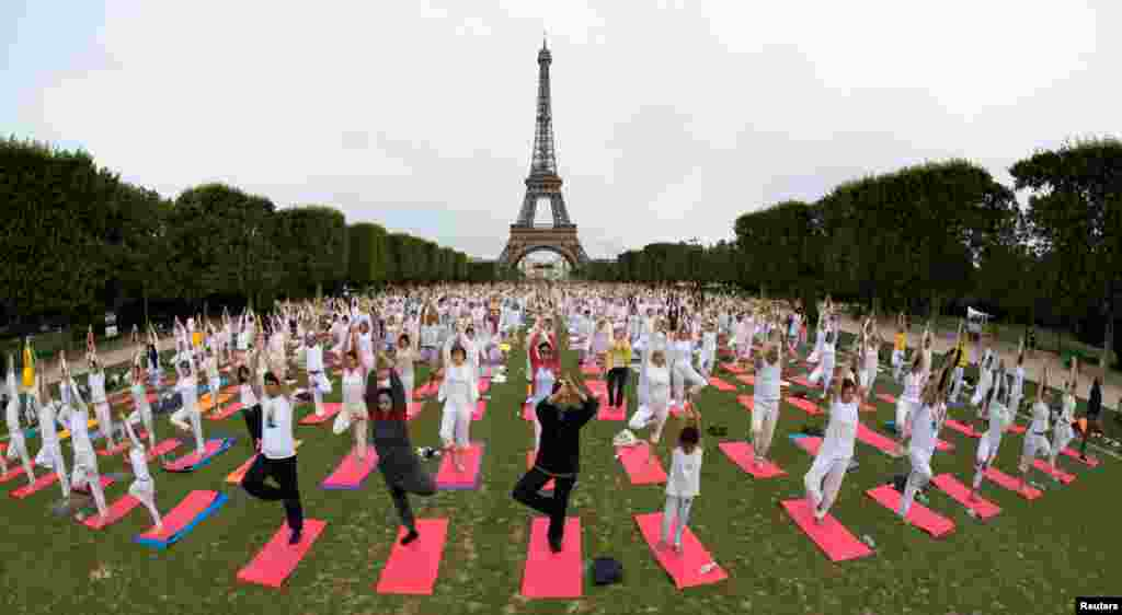 People gather for an open-air yoga session near the Eiffel tower in Paris, France.