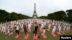 People gather for yoga near the Eiffel tower in Paris, France June 17, 2018. (REUTERS/Philippe Wojazer)