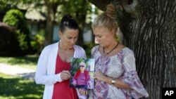 Angela Ermold, right, and her sister, Denise Gracely, hold a photo of their mother, Marian Rauenzahn, Thursday, June 17, 2021, in Fleetwood, Pa. (AP Photo/Matt Slocum)