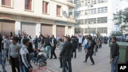 """Algerian youth protesters clash with riot police in Annaba, Algeria. Many held signs reading """"Bouteflika out,"""" in reference to President Abdelaziz Bouteflika, in power since 1999, February 13, 2011"""