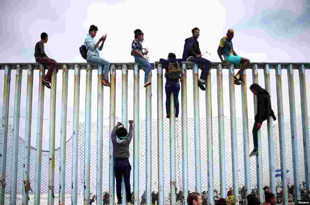 Members of a caravan of migrants from Central America climb up the border fence between Mexico and the U.S., in Tijuana, Mexico, as a part of a demonstration prior to preparations for an asylum request in the U.S., April 29, 2018.
