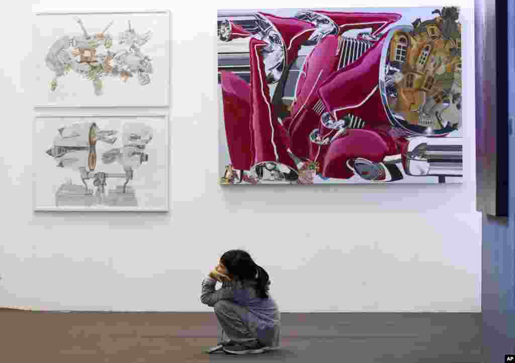 A Chinese child admires a modern art painting displayed at the Art Beijing Exhibition, held at the Agricultural Exhibition Center in Beijing.