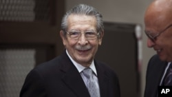 Guatemala's former dictator Jose Efrain Rios Montt, left, smiles as he attends his hearing in Guatemala City, Jan. 28, 2013.