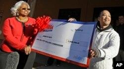 Thuy Nguyen, derecha, acepta un millón de dólares de comisión por haber vendido el número ganador de la Mega Millions en California.