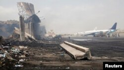 Planes are seen near a section of a damaged building (L) at Jinnah International Airport, after Sunday's attack by Taliban militants in Karachi, June 10, 2014.
