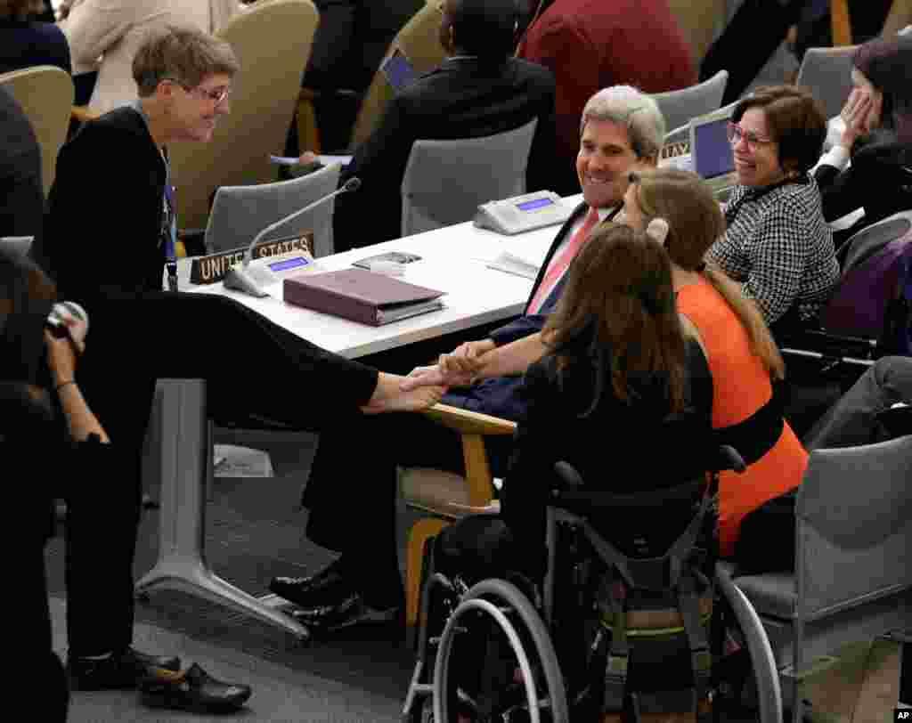 Theresia Degener, quien carece de brazos, miembro del comité de los derechos de las personas con discapacidades saluda con su pie al secretario de Estado John Kerry y a la embajadora de EE.UU. ante la ONU, Samantha Powers durante una reunión de alto nivel sobre discapacidad y desarrollo.