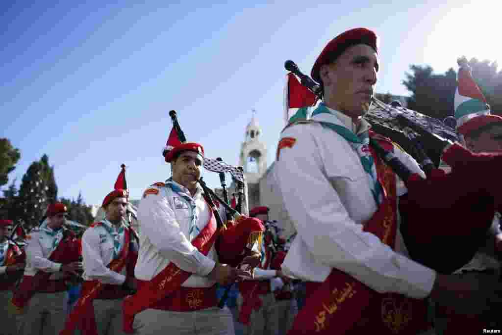Anggota pramuka Palestina berpartisipasi dalam parade prosesi Natal di Alun-Alun Manger, di depan Gereja Nativity tempat kelahiran Yesus (24/12).