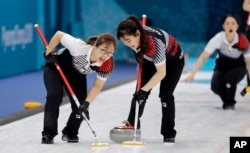 South Korea's Kim Seonyeong, left, sweeps ice with a teammate during their match against Russian athletes at the 2018 Winter Olympics in Gangneung, South Korea, Feb. 21, 2018.