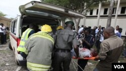 Para petugas mengangkut korban luka-luka peledakan markas PBB di Abuja ke dalam ambulans. 23 orang tewas dalam serangan bom ini (26/8).
