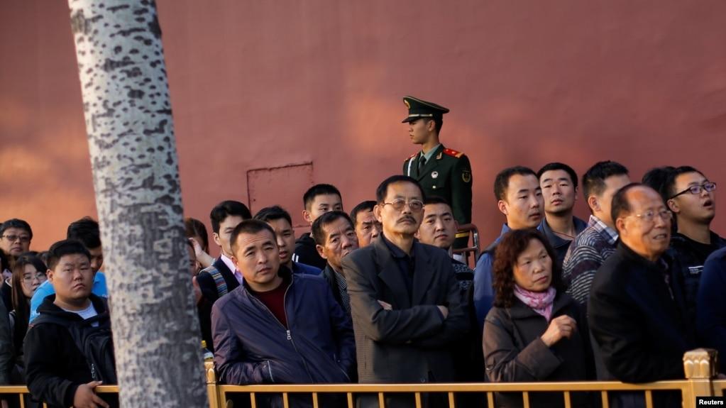 中共十九大举行之际,人们排队等待进入北京天安门广场,有武警站岗(2017年10月22日)