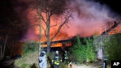 Firefighters stand in front of the burning monkey house at Krefeld Zoo, in Krefeld, Germnay, Wednesday Jan 1, 2020. A fire at a zoo in western Germany killed a large number of animals in the early hours of the new year, authorities said. (Alexander…