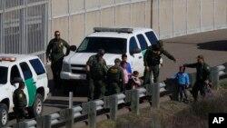 미국 샌디에이고 인근 국경에서 국경단속요원이 멕시코에서 넘어온 불법월경자들을 체포하고 있다.