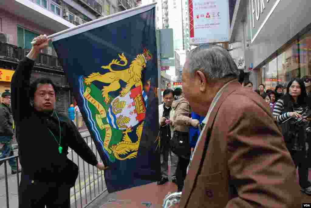 有參加「倒梁」遊行的示威者高舉港英殖民時期的「龍獅旗」,抗議香港主權移交中國15年,香港政府管治今不如昔,有途人質疑示威者否認中國人的身分(美國之音湯惠芸攝)