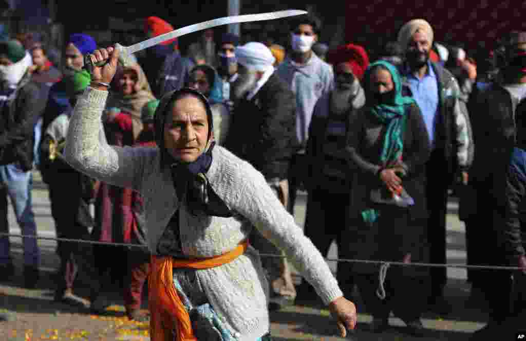 A Sikh woman displays traditional martial art skills during a religious procession ahead of the birth anniversary of Guru Gobind Singh in Jammu, India.