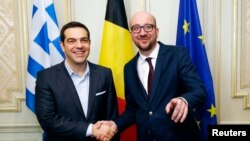 Belgian Prime Minister Charles Michel poses with his Greek counterpart Alexis Tsipras (L) ahead of a meeting in Brussels, Feb. 12, 2015.