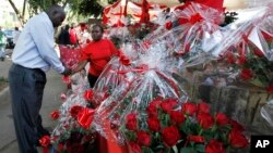 A Kenyan woman sells a bouquet of red roses to a customer for celebrations of Valentine's Day at a flower market in Nairobi, Kenya, February 14, 2012.
