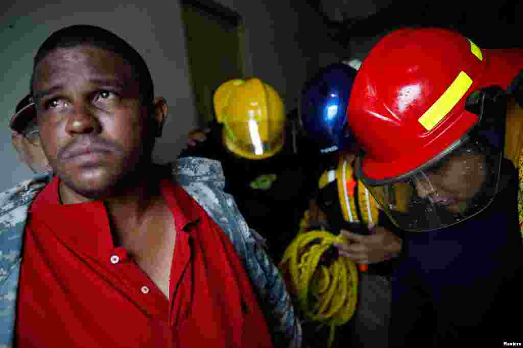 Rescue workers pray before walking out from the Emergency Operation Centre after the area was hit by Hurricane Maria in Guayama, Puerto Rico, Sept. 20, 2017.