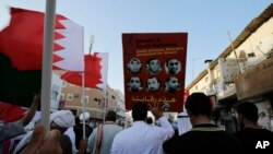Bahraini anti-government protesters wave national flags and raise images of jailed Shiite opposition leader Sheikh Ali Salman and other protesters sentenced to death as they chant slogans demanding their freedom during a protest in Daih, Bahrain, Monday,