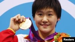 لندن اولمپکس میں خواتین کے 400 میٹر پیراکی کے مقابلوں میں عالمی ریکارڈ بنانے والی چین کی 16 سالہ تیراک یی شیون اپنے گولڈ میڈل کے ساتھ