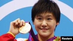 Perenang Tiongkok Ye Shiwen menggengam medali emasnya seusai upacara penyerahan medali untuk para juara renang medley perorangan 400 meter di Olimpiade London 2012 (31/7).