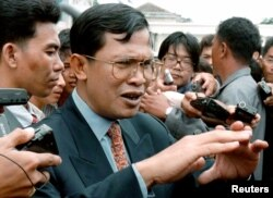 FILE PHOTO - Cambodia's strongman Hun Sen answers journalists' questions as he leaves the National Assembly in Phnom Penh on July 28, 1997. (Reuters)