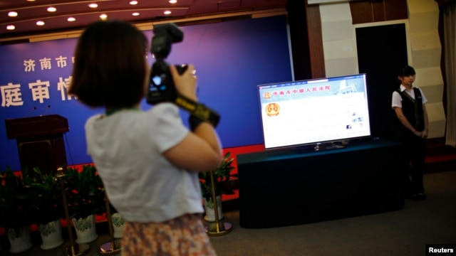A journalist takes pictures near a television screen displaying the Weibo page of Jinan Intermediate People's Court, at the court's media center during the trial of Bo Xilai in Jinan, Shandong province, Aug. 22, 2013.