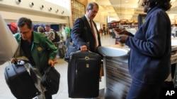 FILE - Passengers check-in their luggage at the Delta counter at Hartsfield-Jackson Atlanta International Airport, in Atlanta, Sept. 27, 2013.