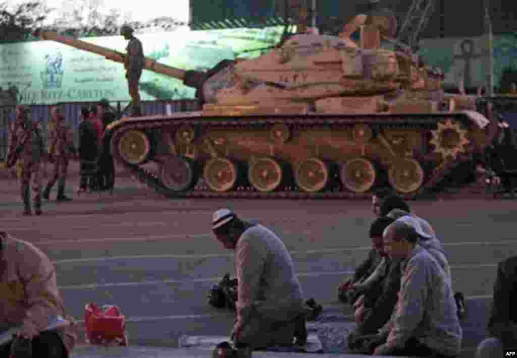 Anti-government protesters offer their evening prayers, in front of an Egyptian army tank securing the area, during a protest in Cairo's Tahrir Square, Egypt, Monday, Jan. 31, 2011. A coalition of opposition groups called for a million people to take to C
