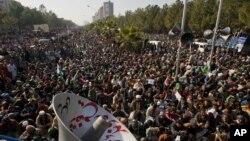 15일 파키스탄 이슬라마바드에서 이틀째 대규모 시위가 열린 가운데, 이슬람 지도자 타히르 울 카드리가 연설을 듣고 있는 시위대.
