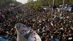 Para pendukung ulama Tahir-ul Qadri mendengarkan pidatonya dalam demonstrasi anti pemerintah di Islamabad, Selasa (15/1).