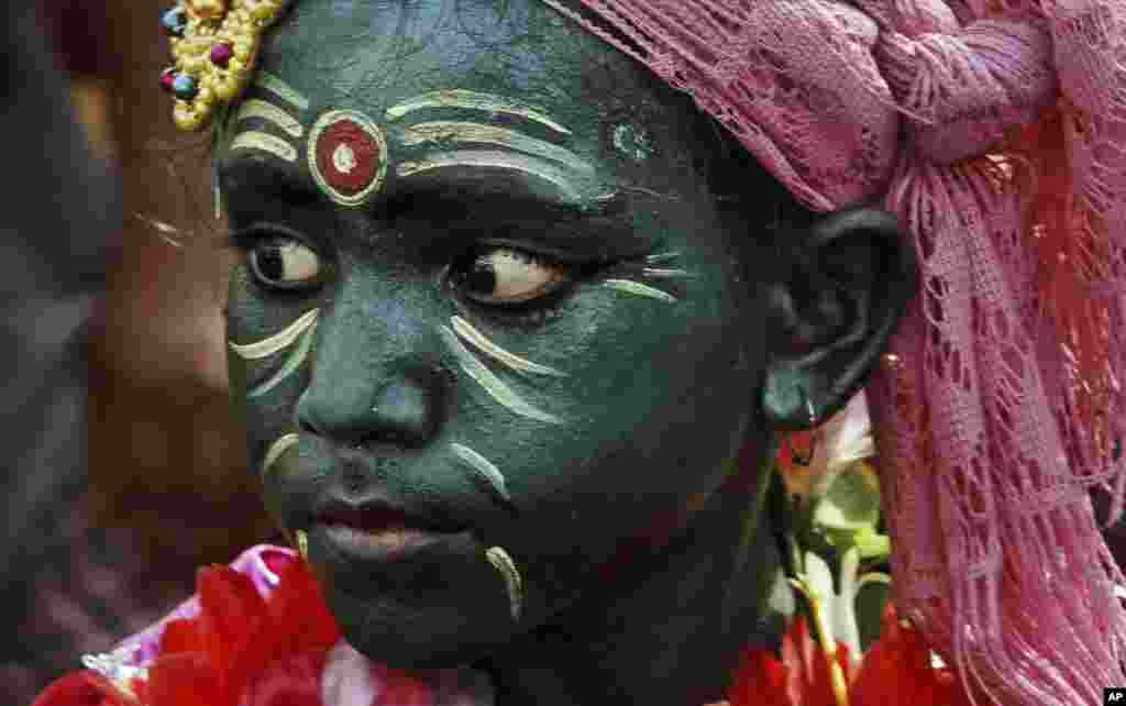 Một cậu bé người Ấn Độ tham gia một đám rước lễ trong lễ hội Yatra Chandan tại Puri, cách thành phố Bhubaneswar phía đông Ấn Độ 65 km. Chandan Yatra, có nghĩa là Hành trình Gỗ Đàn hương, là lễ hội mà tín đồ vẽ mặt thành những vị thần với chất dính từ gỗ đàn hương.