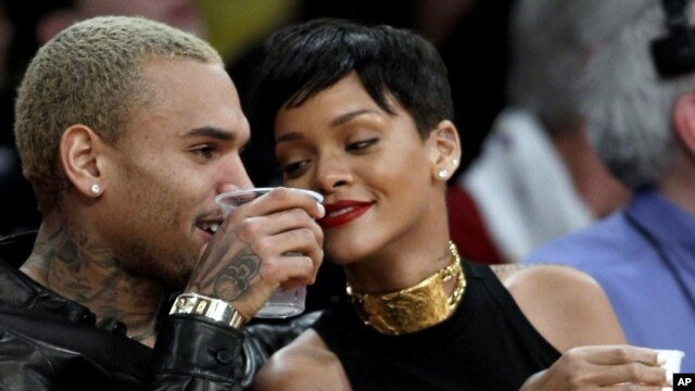 Entertainers Chris Brown, left, and Rihanna attend an NBA basketball game between the Los Angeles Lakers and New York Knicks in Los Angeles, December 25, 2012.