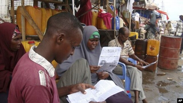 People read local newspapers reporting the death of al-Qaida leader Osama bin Laden, in the streets of Somalia's capital Mogadishu, May 3, 2011