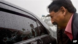 巴蒂的一位朋友在子弹穿过的轿车旁痛哭