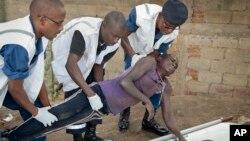 Un homme, pris pour un manifestant opposé au troisième mandat de Pierre Nkurunziza, battu à coup de bar de fer par des membres de la milice des jeunes pro-gouvernement Imbonerakure est porté par des sécouristes en attente d'une ambulance.