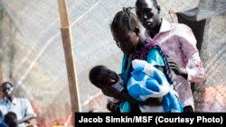 A member of a Doctors Without Borders (MSF) medical team stands near a woman holding her baby on Jan. 10, 2014 at a UN compound in Juba, where thousands have sought refuge from the fighting in South Sudan.