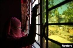 Seorang anak perempuan Rohingya berumur 12 tahun di Bangladesh yang bekerja sebagai pembantu rumah tangga di Bangladesh,memandang keluar jendela di lokasi yang tidak disebutkan, dekat Cox's Bazar, Bangladesh, 8 November 2017.