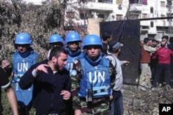 Members of the first U.N. monitoring team, together with members of the Syrian Free Army, visit Homs, Syria, April 21, 2012.