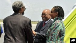 South African president Jacob Zuma (C), flanked by South African ambassador to Ivory Coast Lallie Ntombizodwa (R), shakes hands with African Union representative to Ivory Coast Ambroise Niyonsaba (L) as he arrivesat Abidjan international airport on Februa
