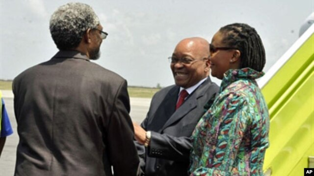 South African president Jacob Zuma (C), flanked by South African ambassador to Ivory Coast Lallie Ntombizodwa (R), shakes hands with African Union representative to Ivory Coast Ambroise Niyonsaba (L) as he arrives at Abidjan international airport on Febru