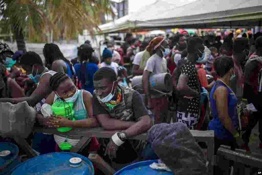 Varios migrantes haitianos se reúnen antes de abordar un bote hacia Capurganá, cerca de la frontera con Panamá, el miércoles 28 de julio de 2021, en Necoclí, Colombia. (AP Foto/Iván Valencia)