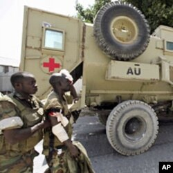 A Ugandan peacekeeper from the African Union Mission in Somalia (AMISOM) assists his wounded colleague after an encounter with Islamist militia in the northern suburbs of Somalia's capital Mogadishu, January 20, 2012