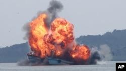 Kapal nelayan asing ilegal yang diledakkan oleh TNI Angkatan Laut di lepas pantai Batam, Oktober 2015. (AP/Kanwa)