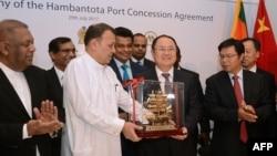 ທ່ານ Mahinda Samarasinghe ລັດຖະມົນຕີທ່າເຮືອ ແລະການຂົນສົ່ງ ຂອງສຣີລັງກາ (ກາງ) ແລກປ່ຽນຂອງຂວັນ ກັບ ຮອງປະທານ ບໍລິສັດ Merchants Port Holdings ຂອງຈີນ Dr. Hu Jianhua.