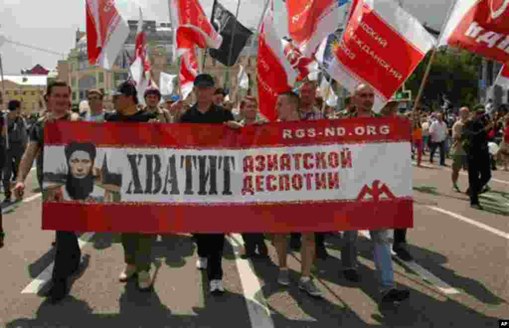 """Opposition members march in central Moscow on Tuesday, June 12, 2012m with a poster depicting president Vladimir Putin reading """"Enough Asian Despotism"""". Tens of thousands of Russians flooded Moscow's tree-lined boulevards Tuesday in the first massive pro"""