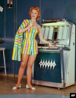 In this 1964 photo, a model stands next to a jukebox.